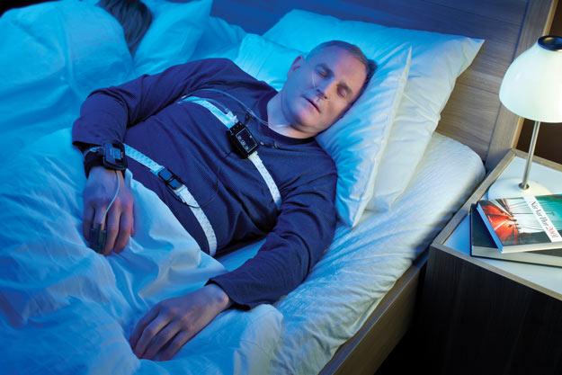 Śpiący mężczyzna używa aparatu diagnostycznego